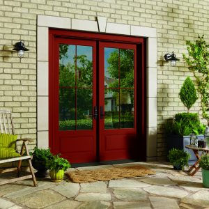 Red entry doors with window and small yard