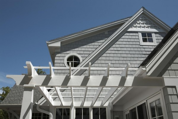 Gray Hardie shingle siding on house with round window