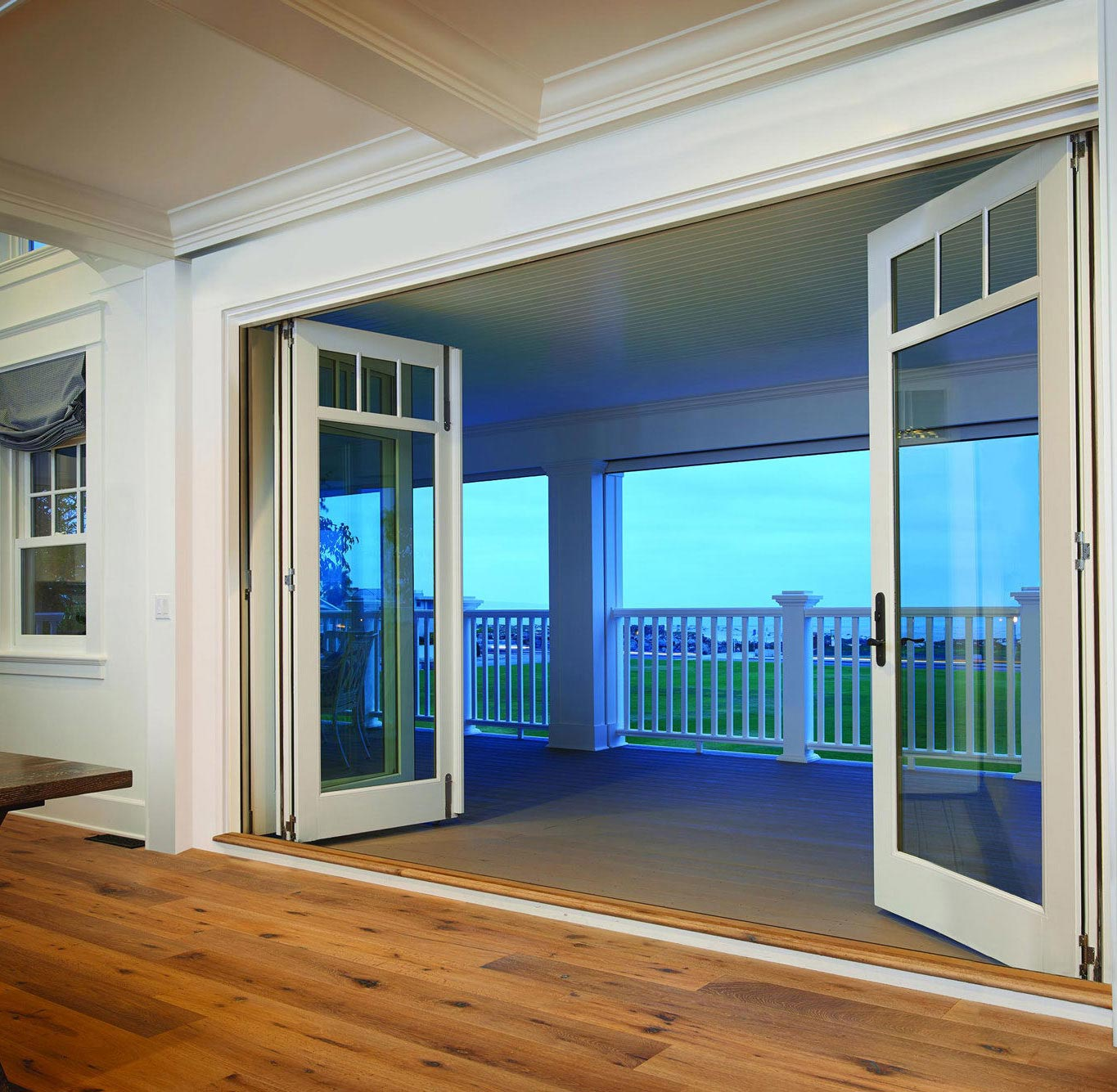 open french doors leading to balcony over grass and ocean